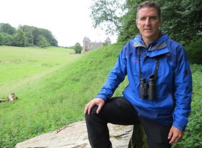 Iolo Williams wearing blue jacket looks at camera - North Wales birding